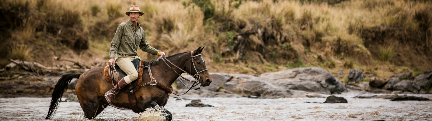 Gordie Church Rides across a river on safari with Safaris Unlimited Kenya Africa